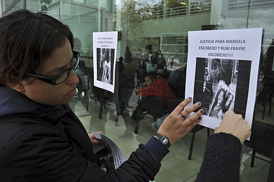 Human rights activists hang a sign on the wall of the state prosecutors office to protest the killing of Marisela Escobedo Ortiz in Ciudad Juarez, Mexico, Friday Dec. 17, 2010.  Escobedo, who had been protesting for three days in front of the governor's office in Chihuahua city to demand justice for her slain daughter, was shot in the head Thursday by unknown assailants in front of the governor's office, authorities said Friday.  The body of Escobedo's daughter, Rubi Frayre Escobedo, was found burned anddismembered in a trash bin in Ciudad Juarez on June 18, 2009 after she went missing for nearly a year. Photo: Raymundo Ruiz, AP