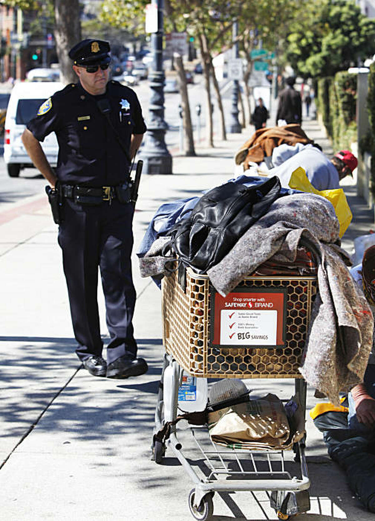 Officer Gary Buckner tells two homeless men that they must move from where they are lying on the sidewalk on Market Street in San Francisco, Calif. on Friday September 10, 2010.