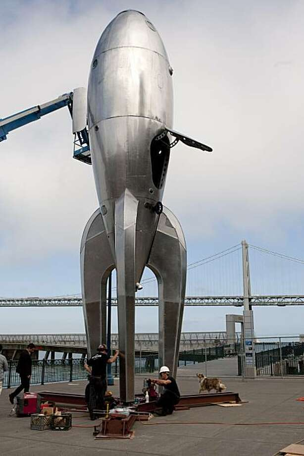 """Crew members install the """"Raygun Gothic Rocketship,"""" a large scuplture of a retro-themed rocket ship, at Pier 14, in San Francisco, Calif., on Thursday, August 4 , 2010. Photo: Laura Morton, Special To The Chronicle"""