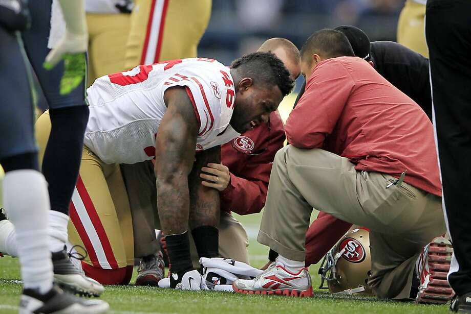 San Francisco 49ers'  Delanie Walker is treated for an injury against the Seattle Seahawks in the first half of an NFL football game Saturday, Dec. 24, 2011. Walker was hurt on a first-down run by Frank Gore in the final minute of the first quarter Saturday against Seattle. Walker was the lead blocker for Gore, but fell as he went through the hole. As he went down, Walker was caught by a knee to the face from Seattle linebacker Leroy Hill, who was trying to jump over Walker as he pursued Gore. (AP Photo/John Froschauer) Photo: John Froschauer, Associated Press