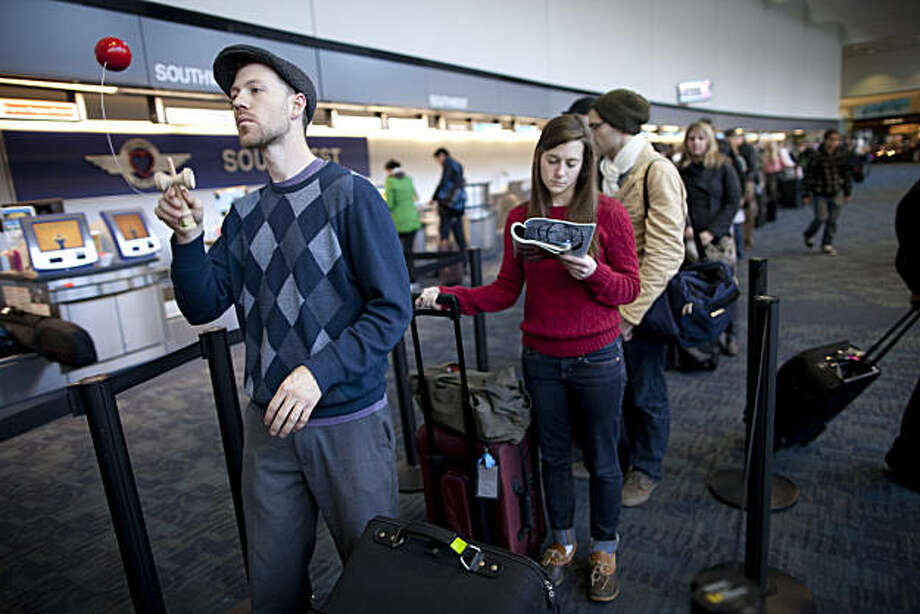 Tim Rice of San Francisco plays with a Kendama as he passes the time waiting to check into his Indiana bound Southwest flight as Jordan Thompson of Berkeley reads a magazine waiting for her Oklahoma bound Southwest flight at San Francisco International Airport on December 20, 2010 in San Francisco, Calif.  Photograph by David Paul Morris/Special to the Chronicle Photo: David Paul Morris, Special To The Chronicle