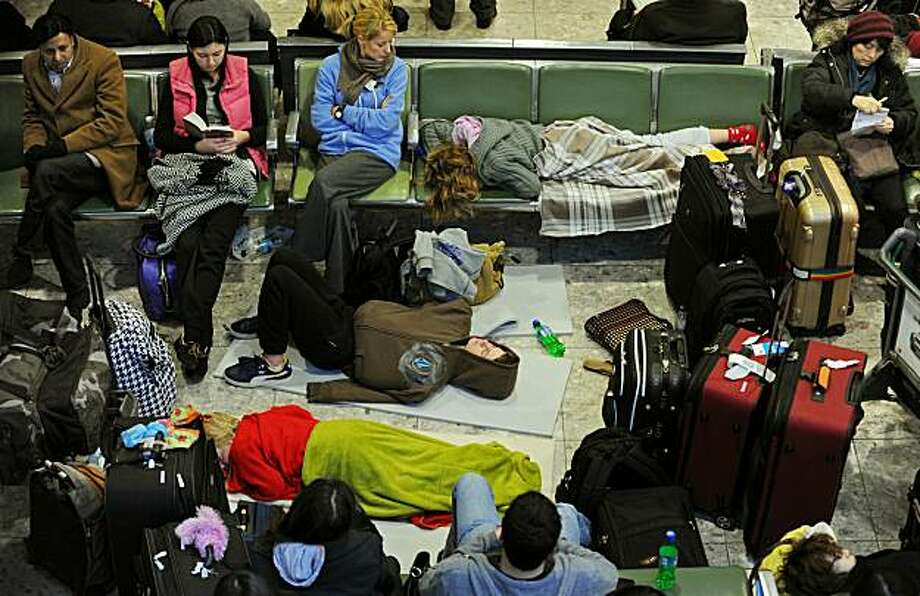 "A passenger lies on the floor, surrounded by luggage and other waiting passengers, at Heathrow Airport's Terminal 3 building, west of London, on December 21, 2010.  Fresh snowfall added to the misery of thousands of Christmas travellers across Europe Tuesday, paralysing flights and trains as the EU lashed out at airports for ""unacceptable"" disruption.  London Heathrow, where passengers have been forced to sleep on terminal floors during four days of chaos, cancelled two thirds of flights while Frankfurt closed for several hours after more snow fell overnight. Photo: Adrian Dennis, AFP/Getty Images"