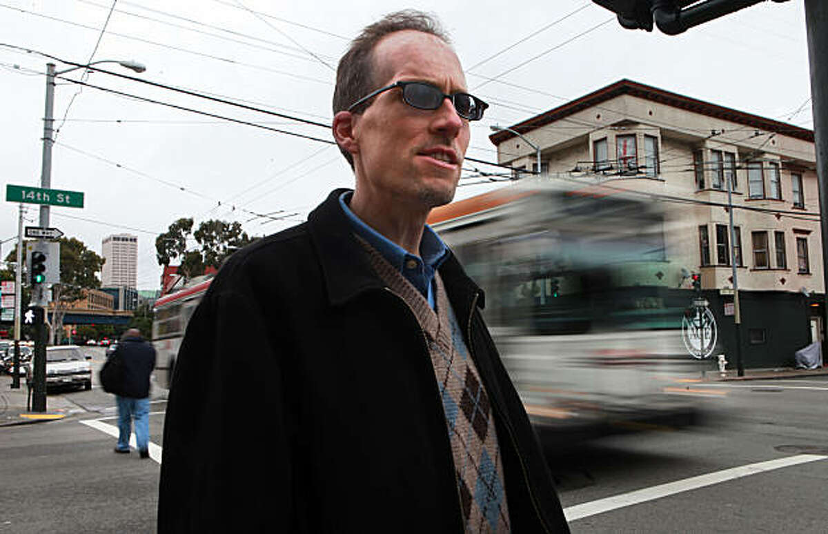 John Alex Lowell standing kitty corner from the crosswalk where he was hit by a car nine years ago at 14th on Mission streets in San Francisco, Calif., remembers eye witness accounts on Tuesday, December 14, 2010. According to witnesses he was dragged to almost the next block suffering serious brain trauma with broken limbs. He is now on the city's pedestrian safety committee.