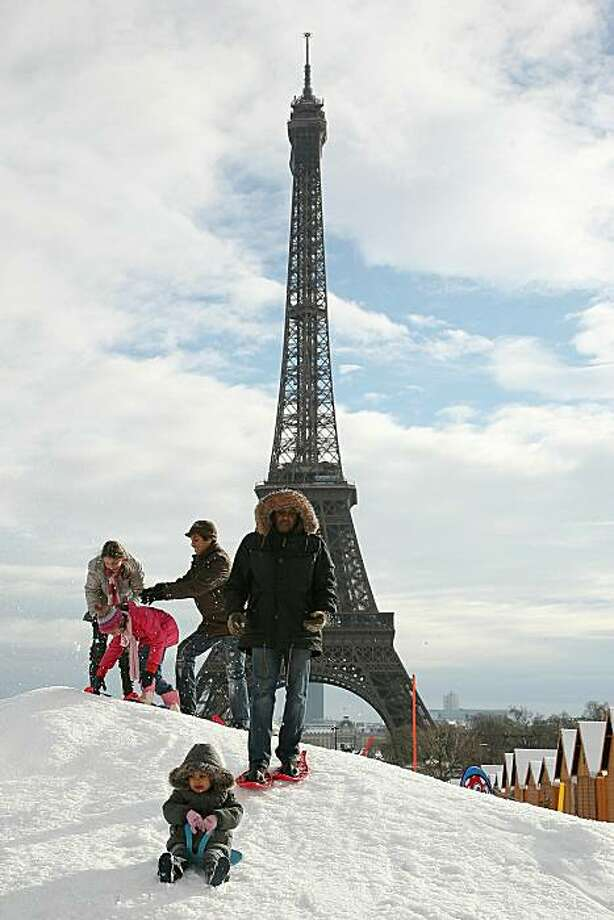 PARIS, FRANCE - DECEMBER 19:  People play in the snow in front of the Eiffel tower on December 19, 2010 in Paris, France.  Parts of Europe saw a large amount of snow this weekend stranding many travelers.  (Photo by Marc Piasecki/Getty Images) *** BESTPIX *** Photo: Marc Piasecki, Getty Images