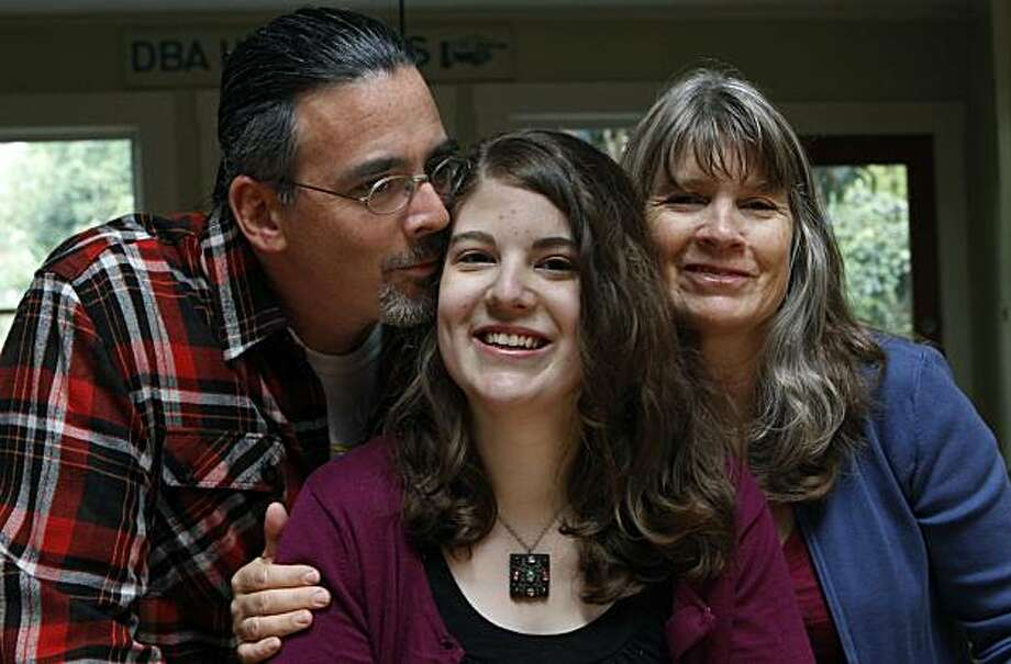 Oona Robertson (center) sits with her father Peter Walbridge and mother Lael Robertson at their home in San Francisco, Calif., on Friday, Nov. 5, 2010. Robertson, 17, has suffered from severe migraines since she was 10 years old and has had to drop out of school as a result. Photo: Paul Chinn, The Chronicle