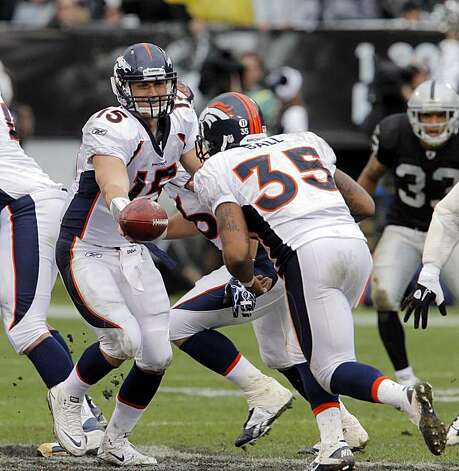 Tim Tebow hands the ball to Lance Ball in the second quarter at the Oakland-Alameda County Coliseum on Sunday. Photo: Carlos Avila Gonzalez, The Chronicle