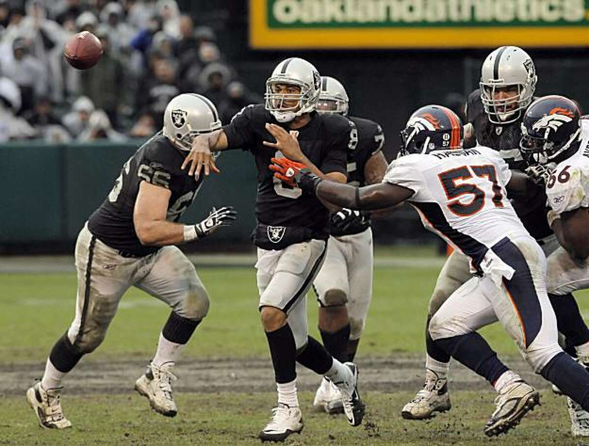 Jason Campbell throws under pressure in the second quarter against the Denver Broncos at the Oakland-Alameda County Coliseum on Sunday.