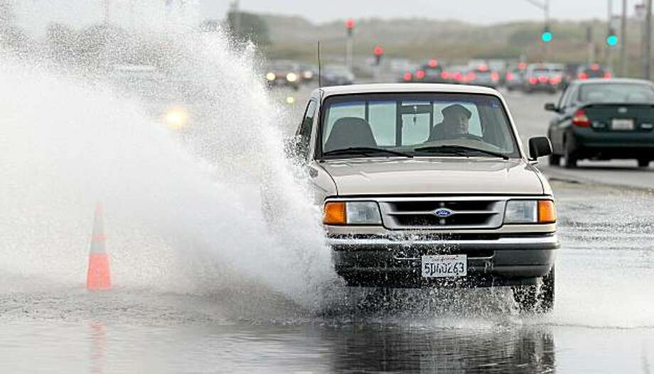 A driver navigates a flooded stretch of the Great Highway in San Francisco on Sunday. Photo: Noah Berger, AP