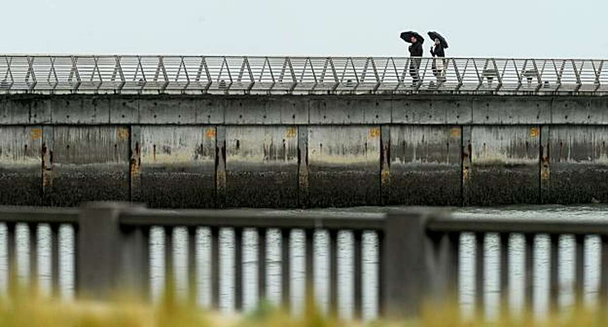 Pedestrians carry take shelter under umbrellas while walking along a pier on Sunday in San Francisco.