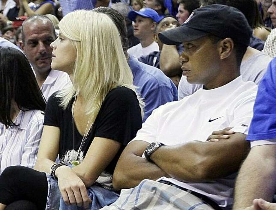 "In this June 11, 2009, file photo, Tiger Woods and his wife, Elin Nordegren watch the fourth quarter of Game 4 of the NBA basketball finals between the Los Angeles Lakers and Orlando Magic in Orlando, Fla.  Tiger Woods said he let his family down with ""transgressions"" he regrets ""with all of my heart,"" and that he will deal with his personal life behind closed doors. His statement Wednesday, Dec. 2, 2009, follows a cover story in Us Weekly magazine that reports a Los Angeles cocktail waitress claims she had a 31-month affair with the world's No. 1 golfer. Photo: David J. Phillip, AP"