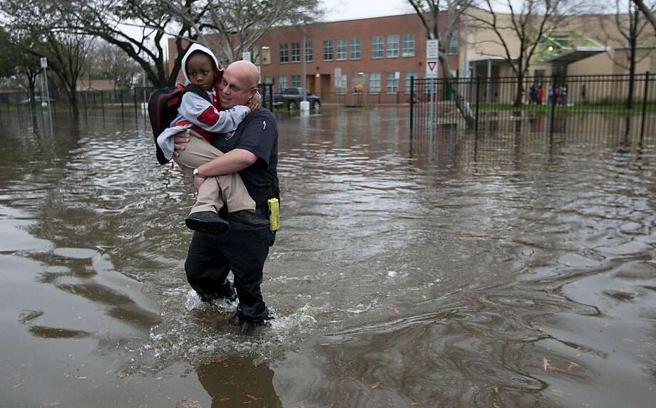 Houston firefighter Scotch Blair carries Dezmund Chapman, 5, through floodwaters to his parents after heavy rain flooded the streets around Peck Elementary School, Monday, Jan. 9, 2012, in Houston. City roads were flooded and thousands of Houston residents lost power Monday after powerful thunderstorms plowed through the area, with a possible tornado damaging and shutting down a nearby mall. (AP Photo/Houston Chronicle, Brett Coomer) MANDATORY CREDIT Photo: Brett Coomer, Associated Press