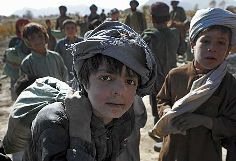 An Afghan boy poses for a photographer as a military convoy form First Battalion, 502nd Infantry Regiment, 101st Airborne Division, stops in Panjwai district, Afghanistan's Kandahar province, Tuesday, Nov. 30, 2010. Photo: Alexander Zemlianichenko, AP