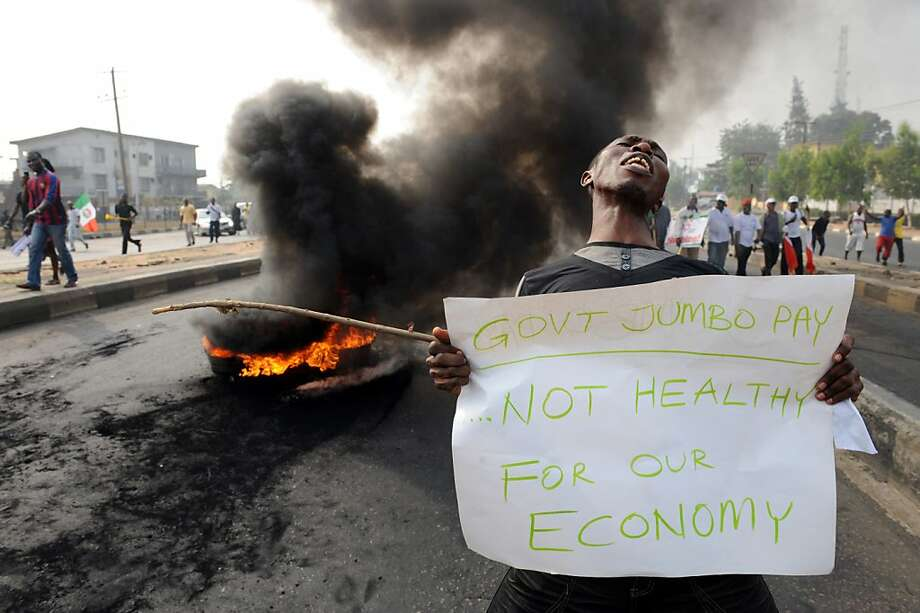 TOPSHOTS A man carries a placard beside a bonfire during a demonstration against soaring petrol prices following government's decision to abolish decades-old fuel subsidies, on January 9, 2012 in Lagos. One protester was shot dead in Nigeria's commercial capital Lagos during the national strike over fuel prices, a union leader said. AFP PHOTO / PIUS UTOMI EKPEI (Photo credit should read PIUS UTOMI EKPEI/AFP/Getty Images) Photo: Pius Utomi Ekpei, AFP/Getty Images