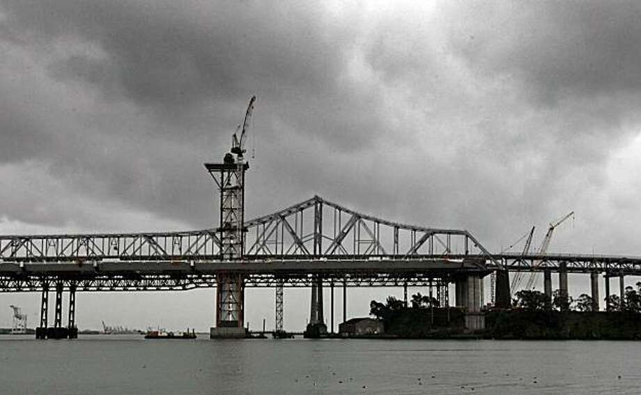 Ironworkers worked through stormy weather, putting in 106 hours to complete the third lift of the new Bay Bridge tower that tops off at 374 feet Saturday. Photo: Lance Iversen, The Chronicle