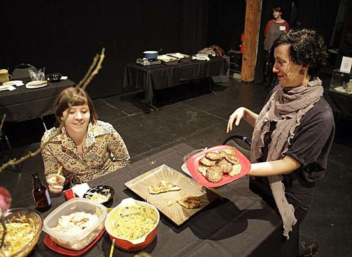 Irina Zadov, right, co-host of Feast of Words, offers latkes to Jessica Langlois during Feast of Words at SOMArts Cultural Center in San Francisco, Calif., on Tuesday, December 7, 2010. A new storytelling potluck, Feast of Words, is gaining a cult following. Once a month, a featured local writer is joined by his or her fans bearing homecooked food at SOMArts Cultural Center for an intimate reading.