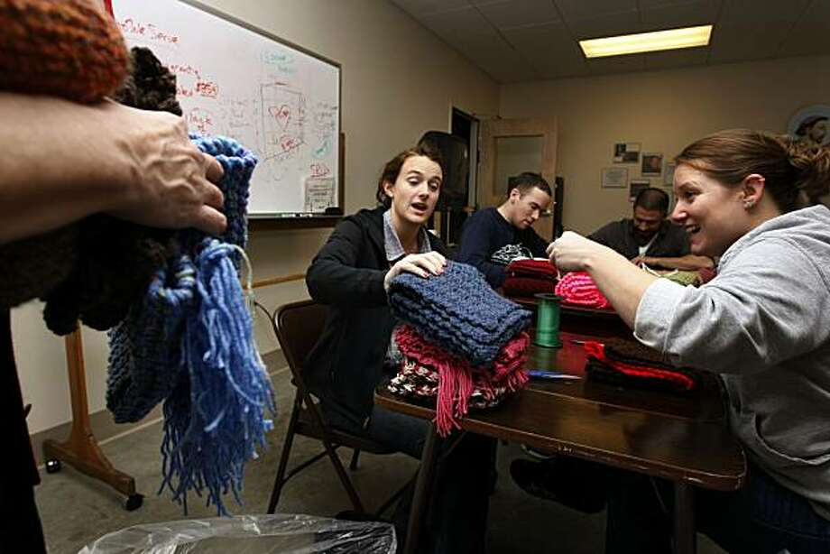 Dana Cunningham, middle, and Jessica Brown prepare scarves to be given to people in need at the St. The Anthony Foundation on Friday, December 10, 2010, San Francisco, Calif. St. The Anthony Foundation hopes to hand out at least least 4,000 warm, hand-knitted scarves that have been donated to the foundation on Christmas Day to the thousands of needy people who line up for a shred of holiday cheer at the foundation's famed kitchen in the Tenderloin. Photo: Adm Golub, The Chronicle