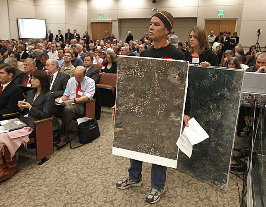 Randy Compton, of Round Mountain, Calif., holds up satellite photos showing forestry clear cuts in Lassen County, while waiting to  testifying before the California Air Resources Board, in Sacramento, Calif., Thursday, Dec. 16, 2010.  The ARB is expectedto vote on whether to adopt sweeping regulations that would give power plants, refineries and other major polluters a financial incentive to reduce their greenhouse gases on California's 2006 climate law, AB32.  Compton was among a group from Shasta County that opposed the forestry protocol of the measure that would allow companies to meet their emission standards  by buying so-called carbon offset credits from lands owned by timber companies that clear-cut up to 40 acres of trees. Photo: Rich Pedroncelli, AP