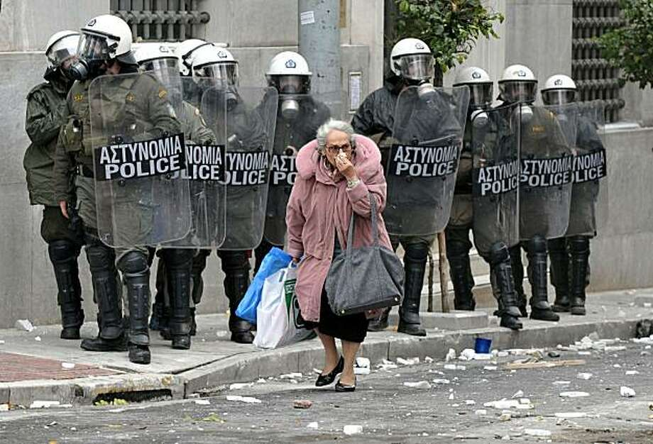 ATHENS, GREECE - DECEMBER 15:  A woman walks past riot police during clashes with protestors December 15, 2010 in Athens, Greece. Violence erupted after approximately 20, 000 protestors marched to parliament during a 24-hour general strike over labor reforms. Protestors reportedly clashed with riot police throughout Athens, buring cars and throwing gasoline bombs.  (Photo by Milos Bicanski/Getty Images)  *** BESTPIX *** Photo: Milos Bicanski, Getty Images