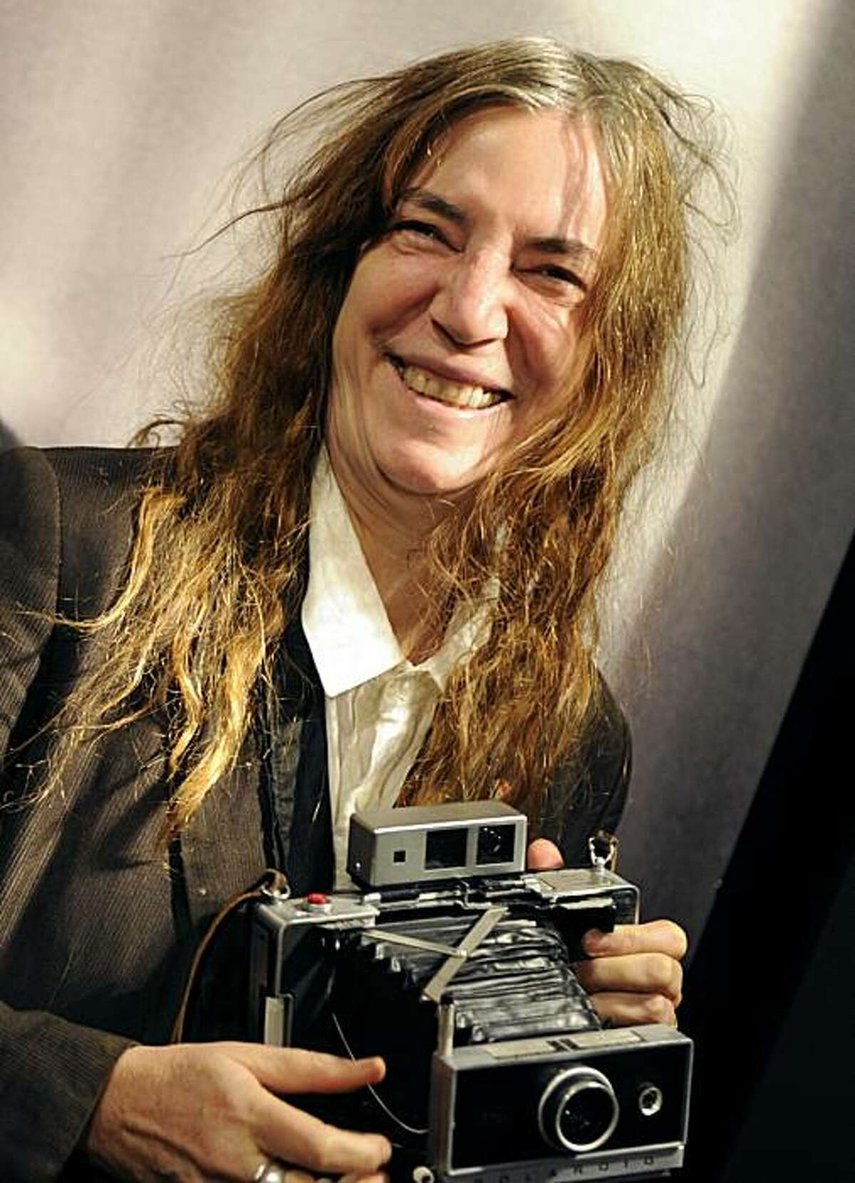 US singer Patti Smith smiles as she takes pictures with her polaroid camera in Madrid on November 26, 2010 during a ceremony at the Casa de America, announcing a week paying tribute to late Chilean writer Roberto Bolano.