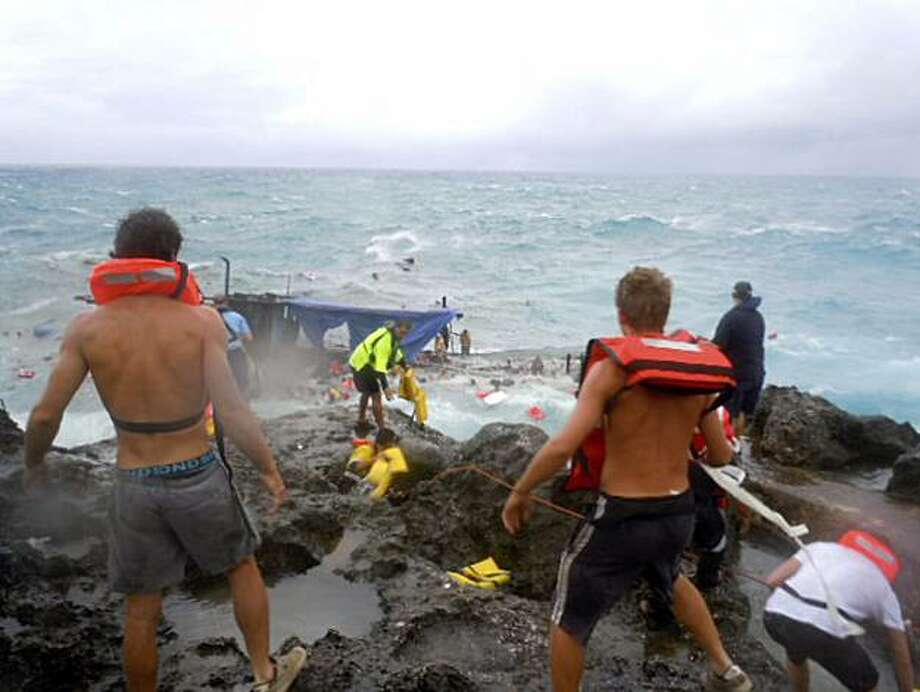 People clamber on the rocky shore on Christmas Island during a rescue attempt as a boat breaks up in the background Wednesday, Dec. 15, 2010. A wooden boat packed with dozens of asylum seekers smashed apart on cliff-side rocks in heavy seas off an Australian island Wednesday, sending some to their deaths in churning whitewater. Photo: Abc, AP