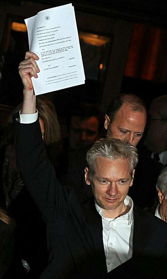 WikiLeaks founder Julian Assange holds up his legal papers as he celebrates outside the High Court in central London, on December 16, 2010. The founder of the WikiLeaks website Julian Assange was granted bail on Thursday by the High Court in London, whichrejected an appeal against him being released even under stringent conditions. TOPSHOTS/ Photo: Ben Stansall, AFP/Getty Images