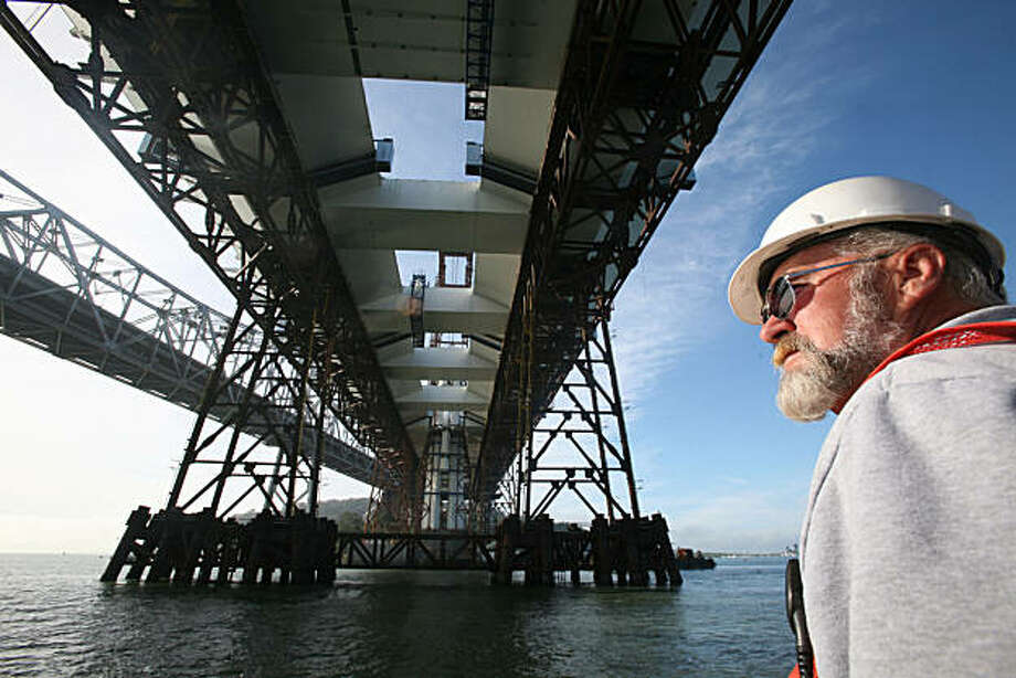 Art Roby, the working boat foreman passes beneath the new section of the Bay Bridge as the 101- feet and 551- ton sections of the tower are lifted into place on the new Bay Bridge Wednesday. It will reach high above the current bridge at 374-feet as seen from the Stella Lind boat in the bay near Treasure Island, Calif. on Wednesday, December 15, 2010.    Kat Wade / Special to the Chronicle Photo: Kat Wade, Special To The Chronicle
