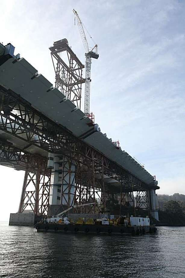 Workers can be seen lifting the 101- feet and 551- ton sections of the tower into place on the new Bay Bridge. Photo: Kat Wade, Special To The Chronicle
