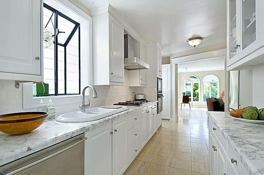 A remodeled kitchen features marble countertops and stainless steel appliances. It connects to a formal dining room. Photo: OpenHomesPhotography.com