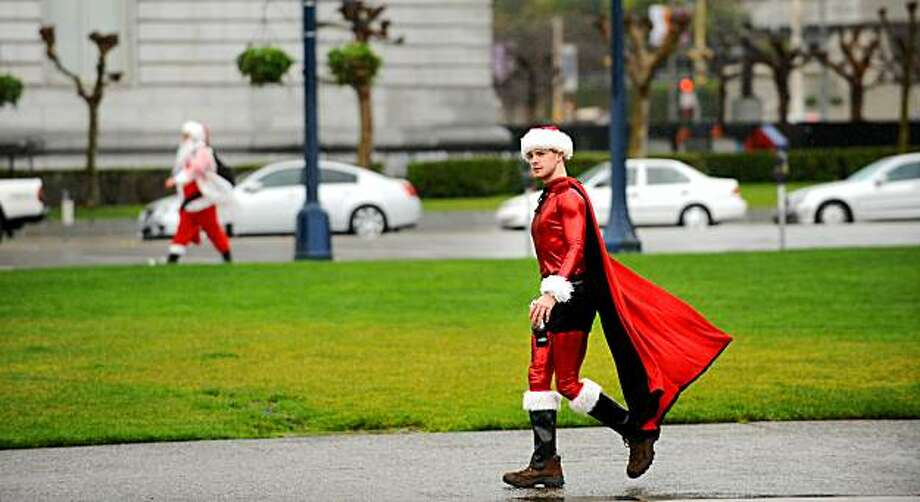 Dressed as Super Santa, Jeff Hicks walks to the starting point of  Santarchy on Saturday in San Francisco. Hicks traveled from Seattle for the event. Photo: Noah Berger, Special To The Chronicle