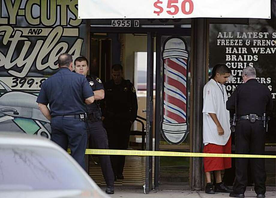 Police investigate the scene of a shooting at Flycuts & Styles in Sacramento, Calif. Tuesday, Dec. 14, 2010, where authorities say a mother loading her 2-year-old son into an SUV was killed and five others were wounded in a gunbattle. Photo: Paul Kitagaki Jr., AP