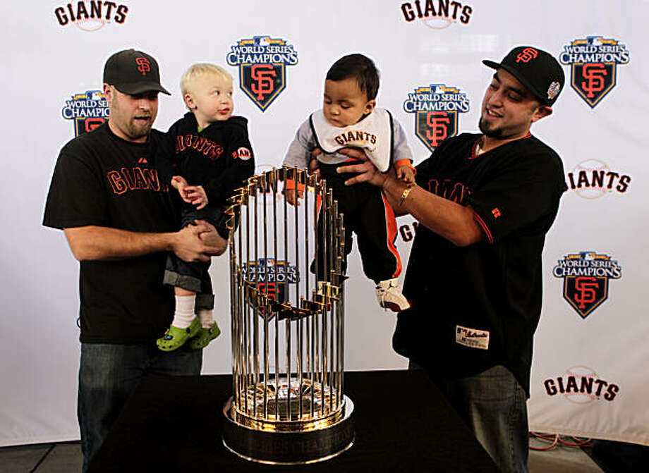 Ryan Stonefelt, left holds son Jason and Luis Diaz holds son Julian to have their picture made with the  World Series Trophy, Monday Dec. 6, 2010, at AT&T Park, in San Francisco, Calif. Thousands of people are expected to have their picture made this week to frame or even to have Christmas ornament made of the image. Photo: Lacy Atkins, The Chronicle
