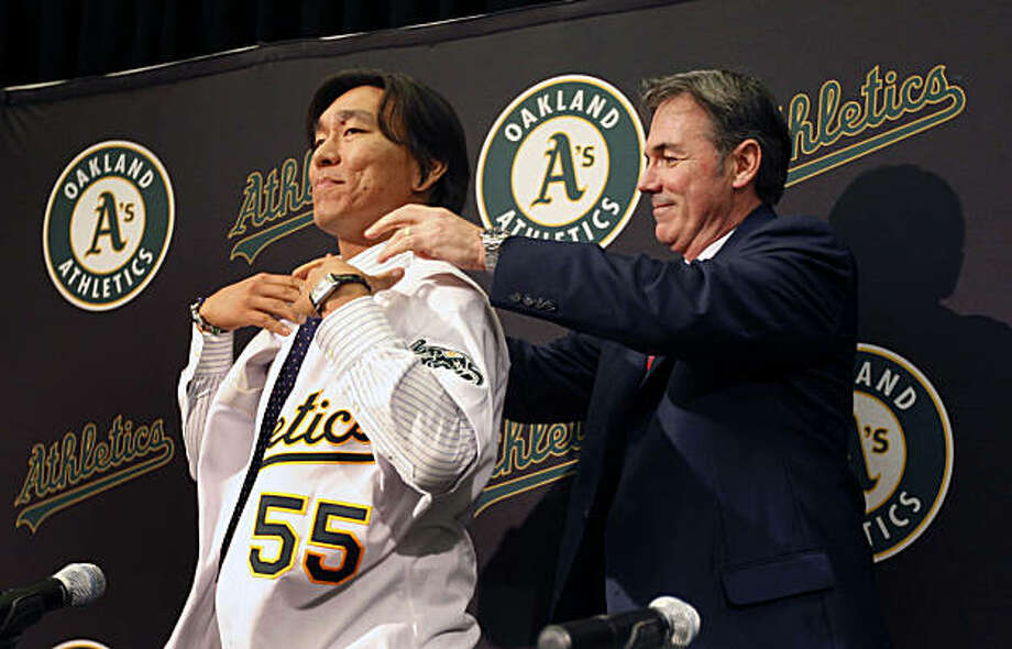 Oakland Athletics General Manager Billy Bean right help Hideki Matsui with his new #55 A's jersey during a press conference at the Oakland Coliseum Tuesday Dec 14, 2010 Photo: Lance Iversen, The Chronicle