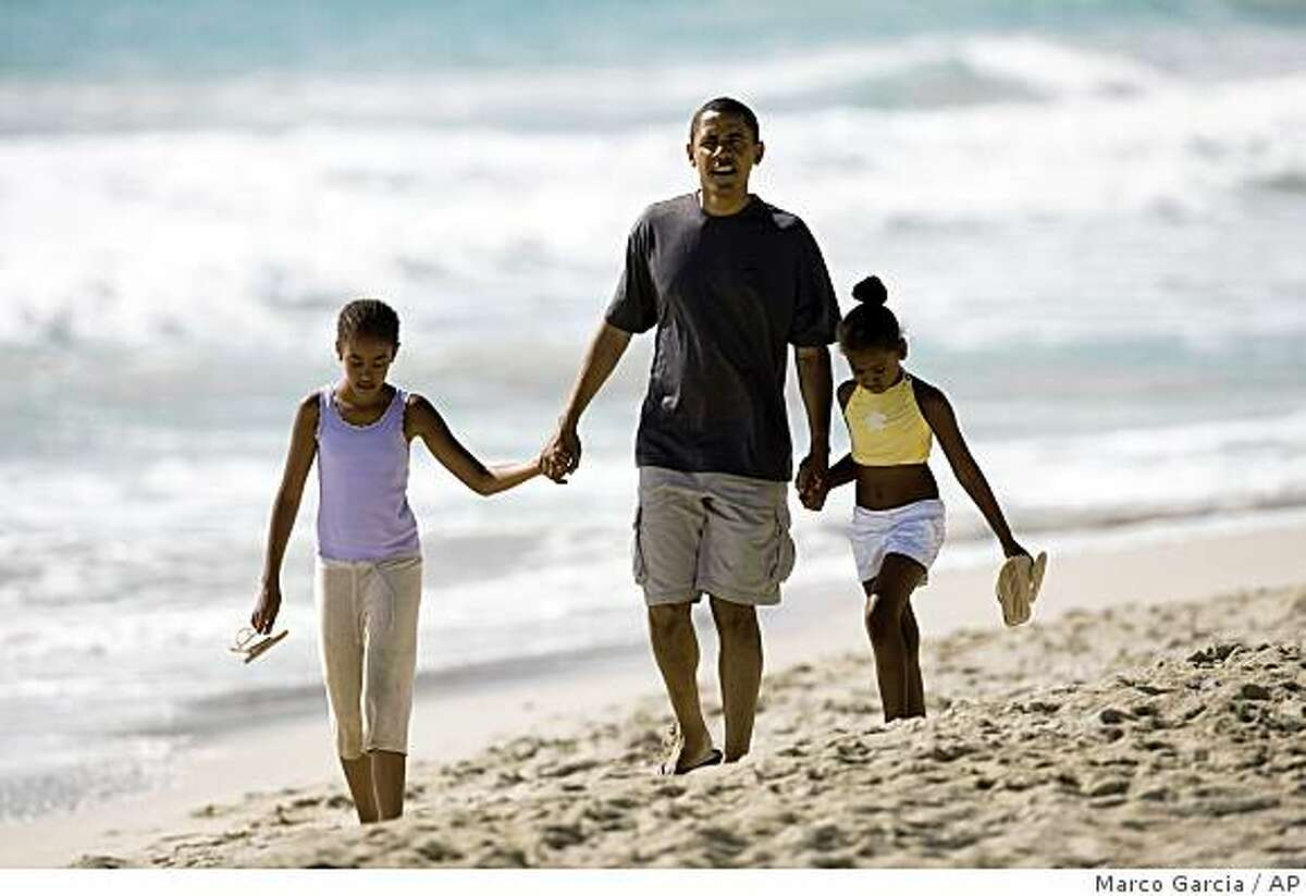 ** CORRECTS LEFT TO RIGHT ** Democratic presidential candidate Sen. Barack Obama, D-Ill. walks down Kailua Beach in Kailua, Hawaii, Tuesday, Aug. 12, 2008, with his daughters Malia, 10, left, and Sasha, 7, during their vacation in Hawaii. (AP Photo/Marco Garcia)