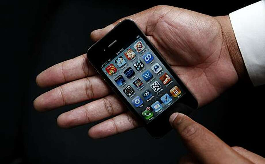 An Associated Press reporter holds the new Apple iPhone during a product test review in San Francisco, Thursday, June 24, 2010. Photo: Jeff Chiu, AP