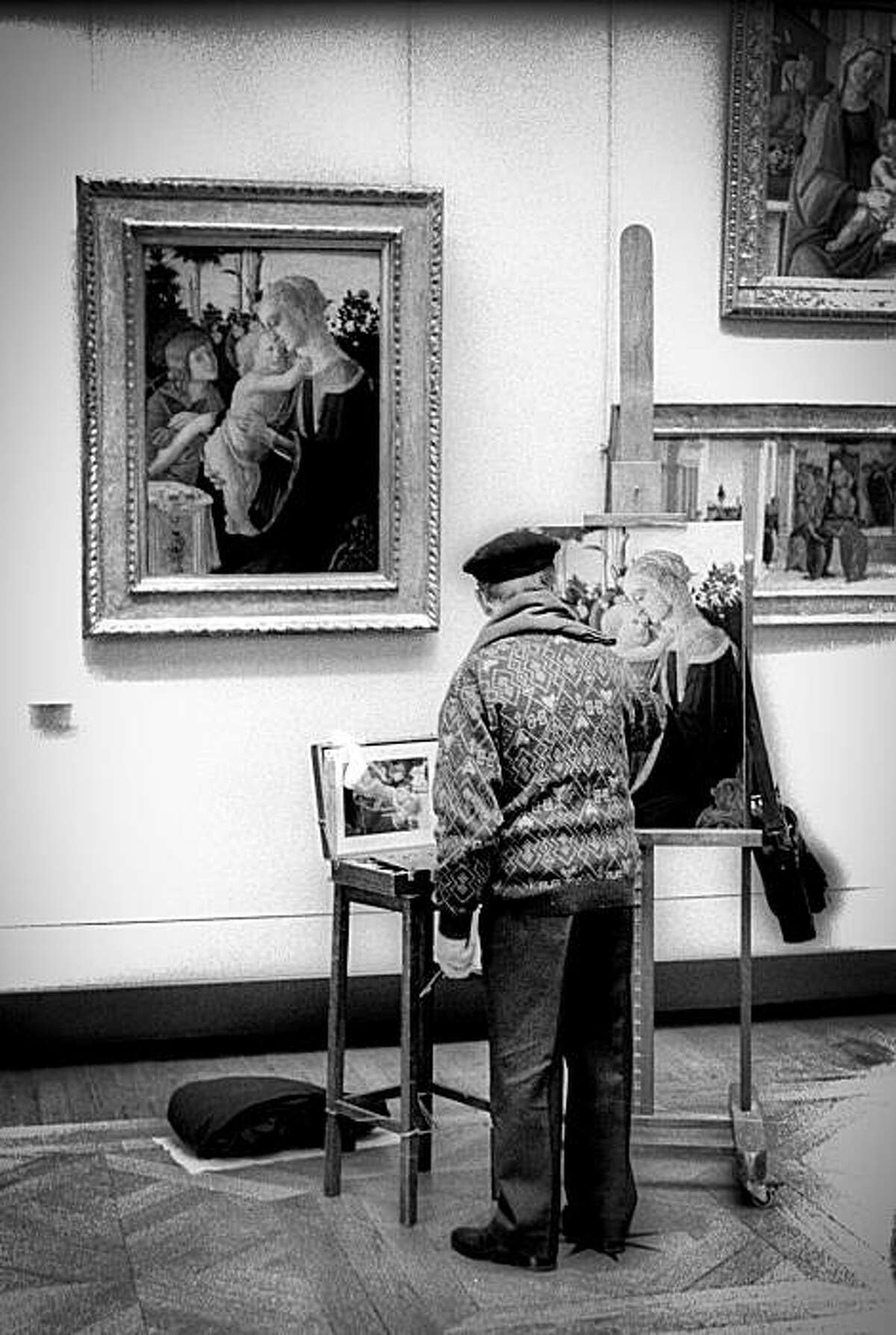 A man copies a painting in the Louvre in Paris, France in 2000.