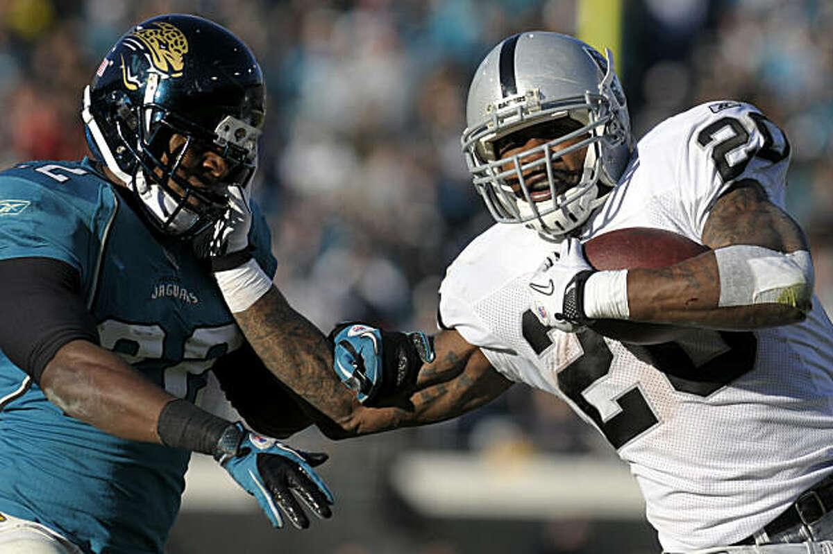 Oakland Raiders running back Darren McFadden (20), right, stiff-arms Jacksonville Jaguars cornerback Don Carey (22) on a 36-yard touchdown run during the second half of an NFL football game in Jacksonville, Fla., Sunday, Dec. 12, 2010. The Jaguars won 38-31.