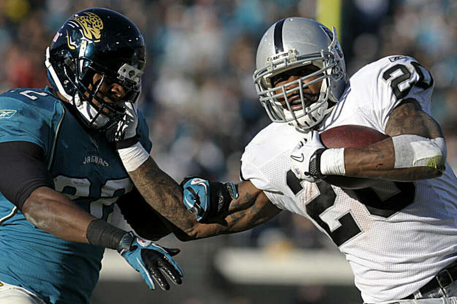 Oakland Raiders running back Darren McFadden (20), right, stiff-arms Jacksonville Jaguars cornerback Don Carey (22) on a 36-yard touchdown run during the second half of an NFL football game in Jacksonville, Fla., Sunday, Dec. 12, 2010. The Jaguars won 38-31. Photo: Phelan M. Ebenhack, AP