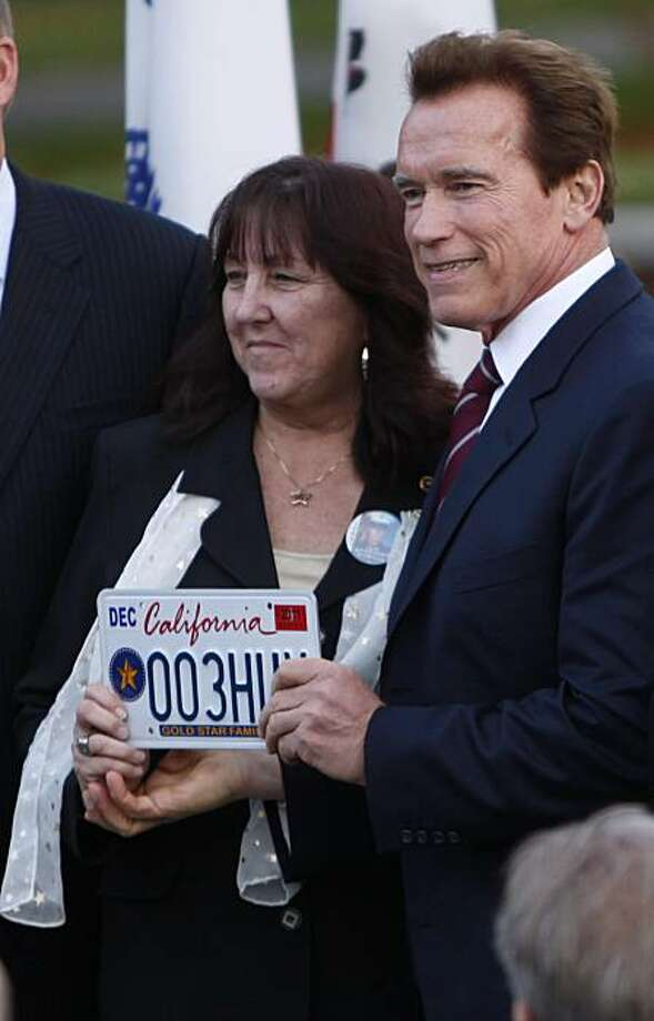 "Dianne Layfield, of Fremont, poses with Gov. Arnold Schwarzenegger after she was presented one of the first three  ""Gold Star Family License Plates"" issued by the Department of Motor Vehicles at Capitol Park in Sacramento, Calif., Thursday, Dec. 9, 2010.Created by the passage of a 2008 measure,  by state Senators Dave Cogdill, R-Modesto, and Jeff Denham, R-Merced, that  enables families who have lost an active duty member of the U.S. Armed Forces  in current and prior wars to obtain a Gold Star plate  honoring their families sacrifice.  Marine Lance Corporal Travis Layfield was killed in an ambush in Iraq in 2004. Photo: Rich Pedroncelli, AP"