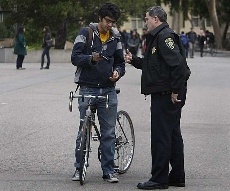 "UC police officer Lawrence Green issues a verbal warning to Gobind Bagai, who was caught riding his bicycle through the designated dismount zone near Wheeler Hall at UC Berkeley on Thursday, Dec. 2, 2010. Officer Green said bicycle riders create an ""uncomfortable environment for pedestrians"" in the heavily-populated Sproul Plaza area during lunchtime. Green also said that many officers feel uncomfortable with the excessive fines and hope that they may be lowered. Fines for riding bicycles through the restricted area are currently as high as $220. Photo: Paul Chinn, The Chronicle"