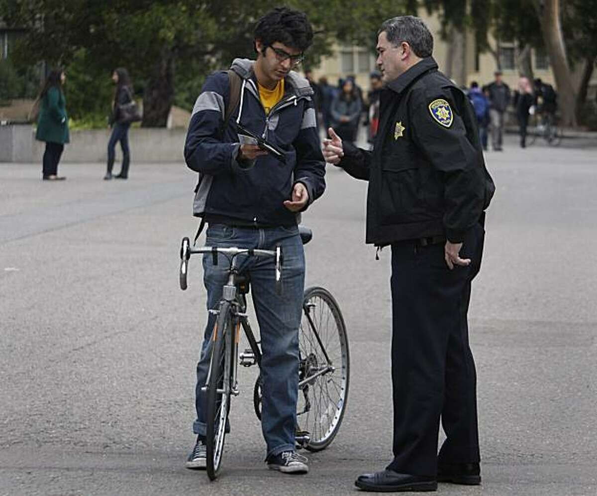 UC police officer Lawrence Green issues a verbal warning to Gobind Bagai, who was caught riding his bicycle through the designated dismount zone near Wheeler Hall at UC Berkeley on Thursday, Dec. 2, 2010. Officer Green said bicycle riders create an
