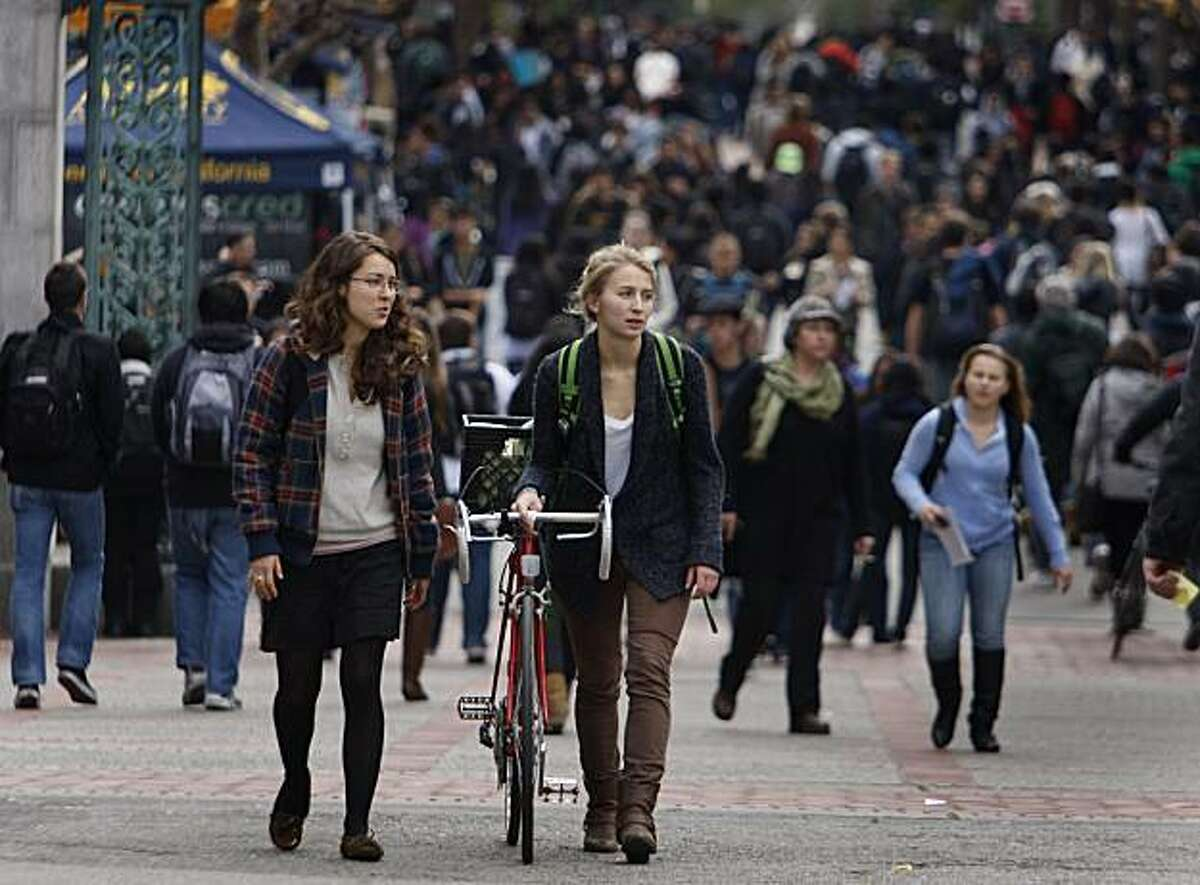 Corinne Jansen (right) walks her bicycle through the designated dismount zone near Sather Gate with her friend Rachel Ely at UC Berkeley on Thursday, Dec. 2, 2010. Fines for riding bicycles through the restricted area are as high as $220.