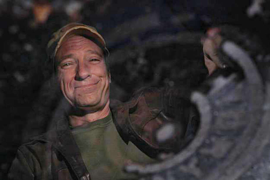 """Mike Rowe, host of """"Dirty Jobs"""" on the Discovery channel is seen reflected in a puddle next to a drain on Monday, November 29, 2010 in San Francisco, Calif. Photo: Lea Suzuki, The Chronicle"""