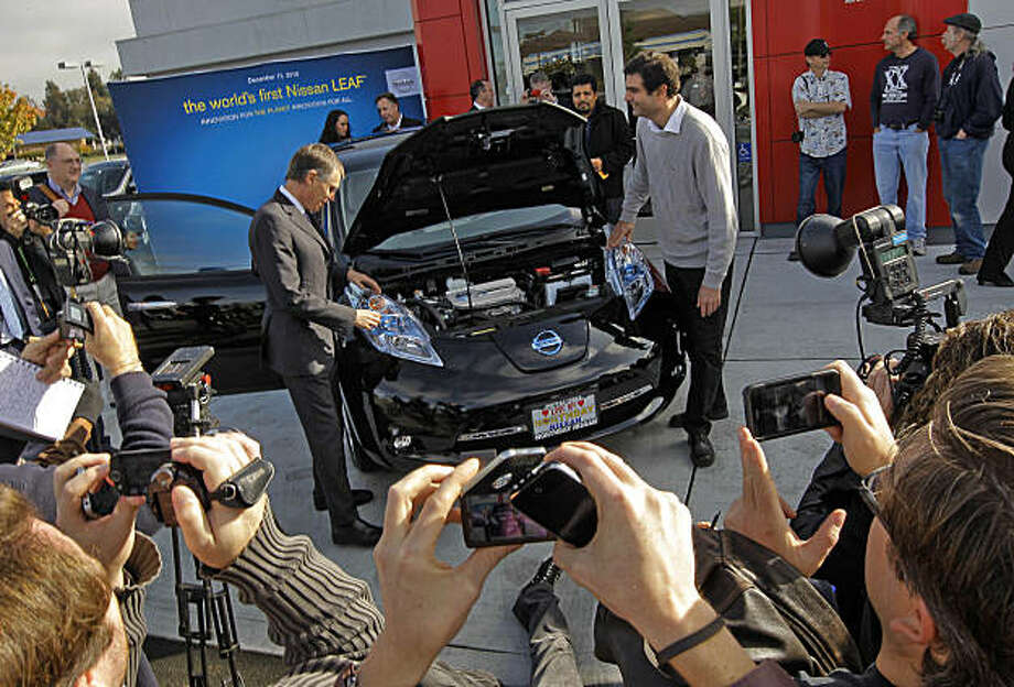Chairman of Nissan America's, Carlos Tavarez, (left) unveils the new vehicle to Olivier Chalouhi, (right) of Redwood City on Saturday Dec. 11, 2010. Chalouhi, is the first owner to receive the new all electric vehicle, the Nissan Leaf.  North Bay Nissan in Petaluma, Ca. was the Bay Area dealership that delivered the brand new car. Photo: Michael Macor, The Chronicle