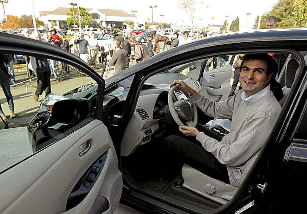Olivier Chalouhi, (center) of Redwood City, checks out the interior of his new vehicle, on Saturday Dec. 11, 2010. Chalouhi, is the first owner to receive the new all electric vehicle, the Nissan Leaf. North Bay Nissan in Petaluma, Ca. was the Bay Area dealership that delivered the brand new car.