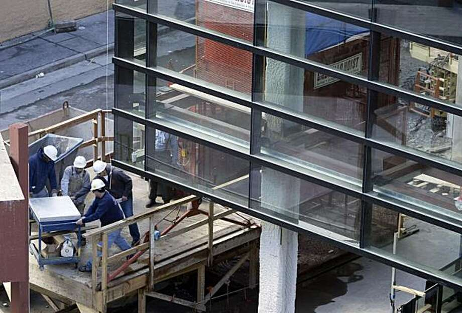 Construction workers (lower left) remove material beneath newly installed glass panels.  Several large glass panels have been attached to the Mission St. facade of the Bloomingdale's project on 2/18/05 in San Francisco, CA. Photo: Paul Chinn, The Chronicle