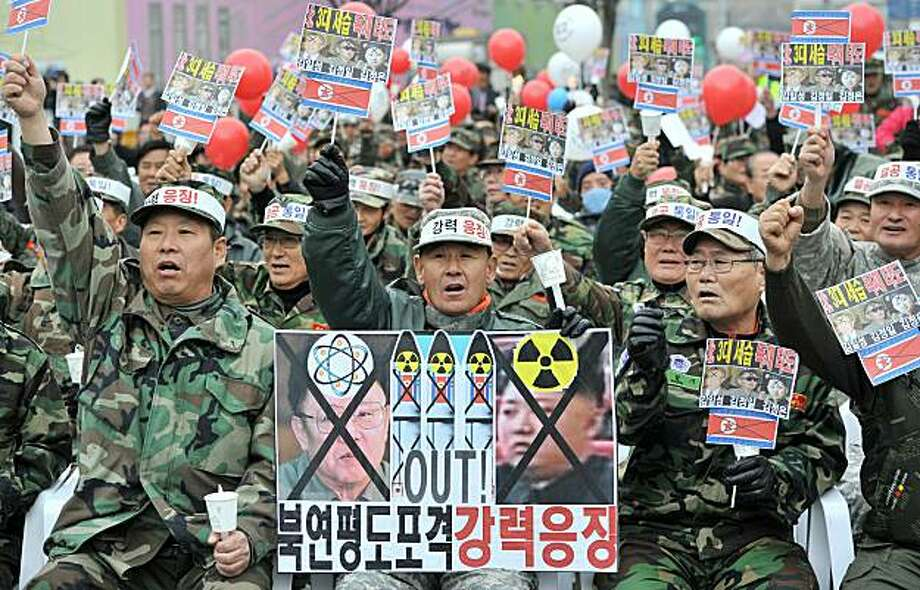 South Korean veterans shout slogans with a placard showing portraits of North Korean leader Kim Jong-Il (L) and his son Jong-Un (R) during a rally in Seoul on December 2, 2010 denouncing North Korea's November 23 artillery attack on Yeonpyeong island. South Korea on December 2, readied plans for more live fire drills as a warning to North Korea and scheduled talks with the United States and Japan on dealing with the volatile nuclear-armed regime. Photo: Jung Yeon-je, AFP/Getty Images