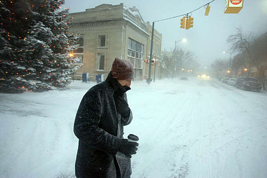 Jamie Al-Shamma, of Traverse City, Mich., sips coffee as he walks in heavy snowfall Sunday, Dec. 12, 2010 toward his vehicle so he can pick up his wife, son and daughter who are also downtown. Photo: Keith King, AP