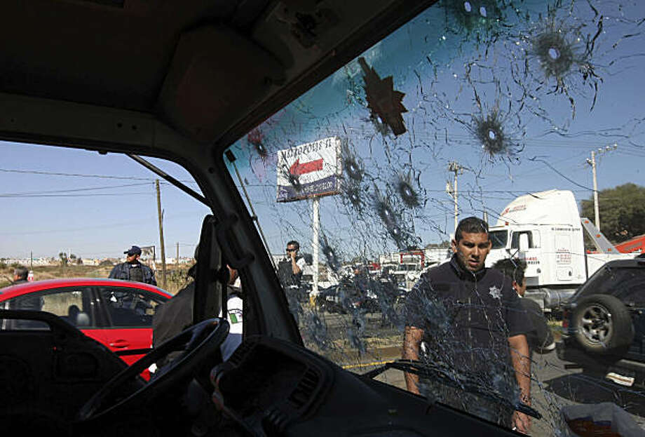 A police officer is seen through a bullet riddled truck window on a road leading to the city of Morelia, Mexico, Thursday Dec. 9, 2010. Gunmen arrived at all five roads leading into Morelia, fired into the air and forced people from their vehicles, according to Michoacan state attorney general office spokesman Jonathan Arrendondo. Photo: AP