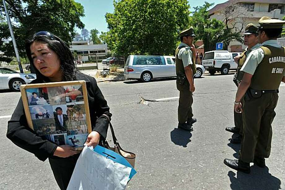 "Clara Aravena, sister of Juan Aravena, an inmate who died during a fire at San Miguel prison, holds up pictures of her brother in front of the Legal Health Service centre in Santiago on December 9, 2010. A fire killed at least 83 inmates in the prison early Wednesday in what officials said was the worst ever disaster on record in Chile's overcrowded and ""inhumane"" prison system. TOPSHOTS/ Photo: Claudio Santana, AFP/Getty Images"