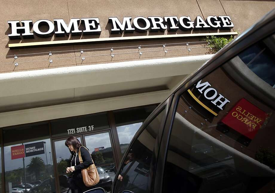 A woman walks past a Wells Fargo Home Mortgage office in La Habra, Calif., Thursday, Oct. 7, 2010. Rates on 30-year mortgages  fell to a new low for the ninth time in 12 weeks, pushed down by traders anticipating a likely move by the Federal Reserve to pump more money into the economy. Photo: Jae C. Hong, AP